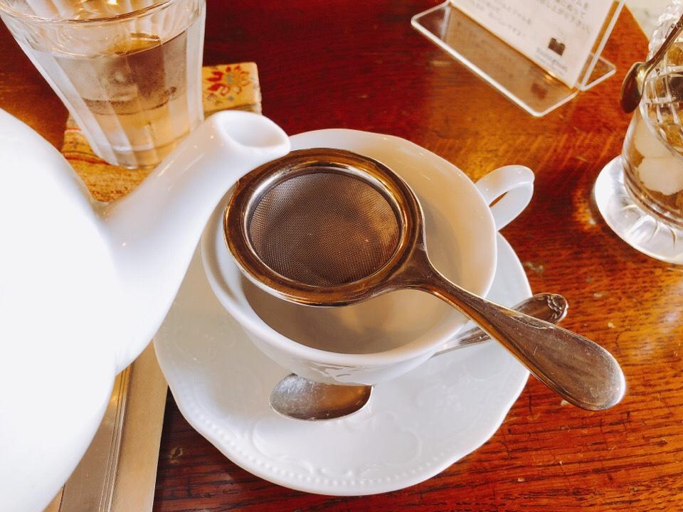 砂時計の砂がなくなったらポットから茶こしを通してカップに注ぎます